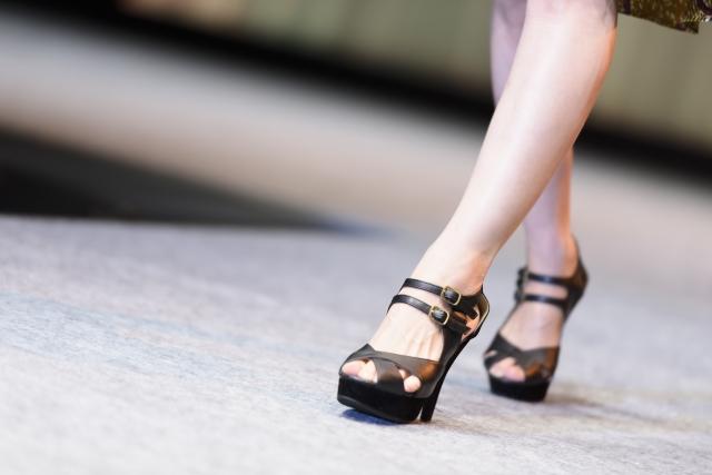 足をクロスさせて歩く女子